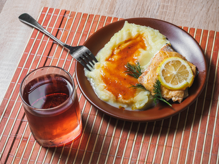 Fried fish with mashed potato and tea. Cafe table.