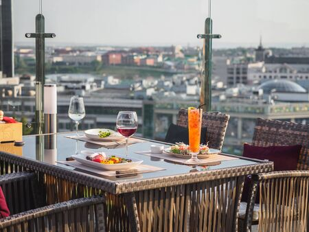 Sky cafe on the roof terrace with view of modern city.