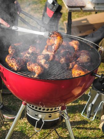 Coocking chicken legs in bbq grill festival.