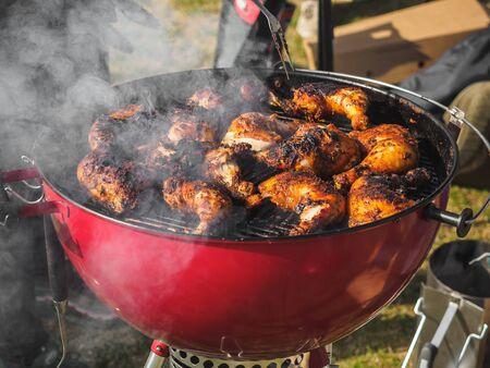 Coocking chicken legs in bbq grill festival.