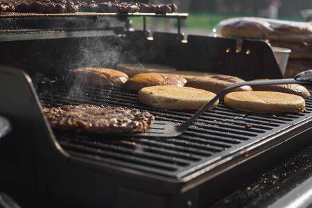 Cooking burgers with beef meat in grill bbq street festival.