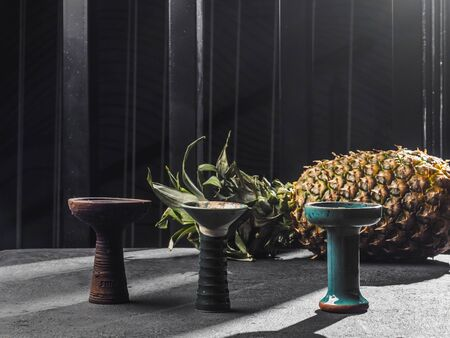 Three hookah bowls with pineapple. Black background.