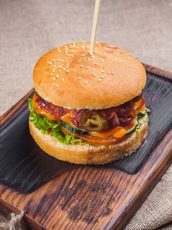 Burger with cheese, tomato, jalapeno, lettuce on the board. Stockfoto - 132262209