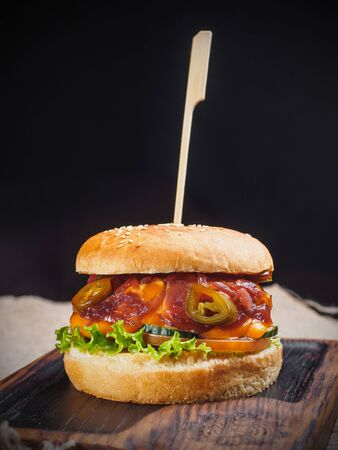 Burger with cheese, tomato, jalapeno, lettuce on the board. Stockfoto - 132262404