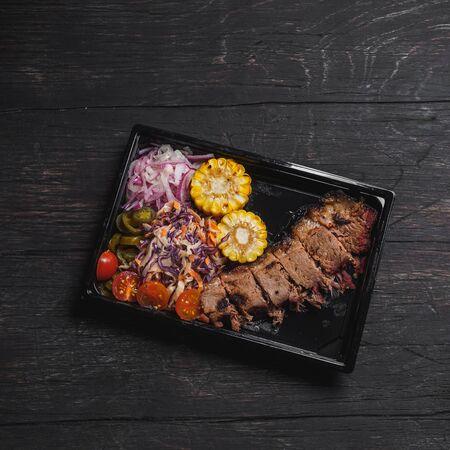 Beef brisket with garnish in plastic black plate.