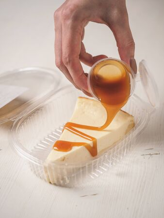 White cheesecake with caramel on plastic box.