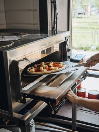 Cooking in modern pizza oven in cafe kitchen.