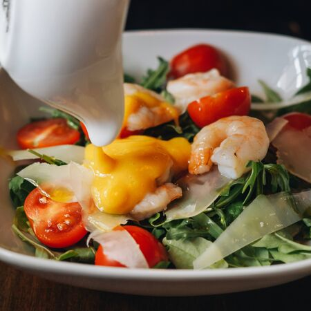 Salad with shrimps mango sauce cheese cherry greens.