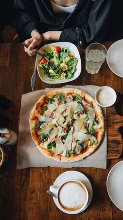 Pizza with parma ham, cheese, arugula, sauce in rustic cafe table. Stockfoto