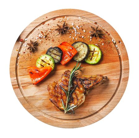 Grilled beef steak with vegetables on wooden board. Isolated