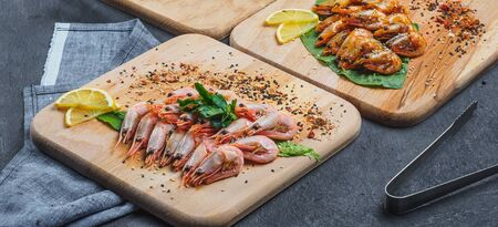 Raw and fried shrimps with lemon on wooden board. Stockfoto