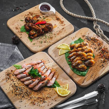 Shrimps with lemon and fried chicken wings on wooden board. Stockfoto
