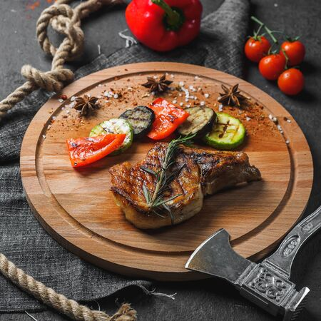 Grilled beef steak with vegetables on wooden board.