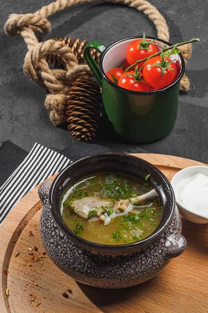 Chicken soup with dill on wooden board.