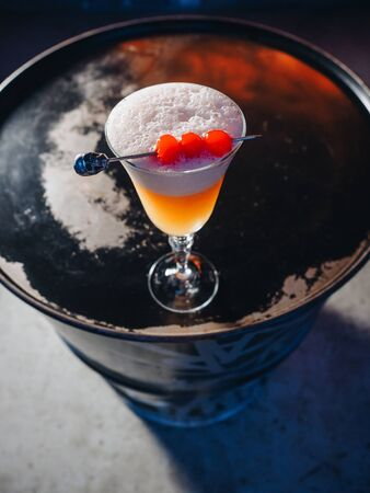 Yellow orange cocktail with cherry skewer on the barrel. Stockfoto