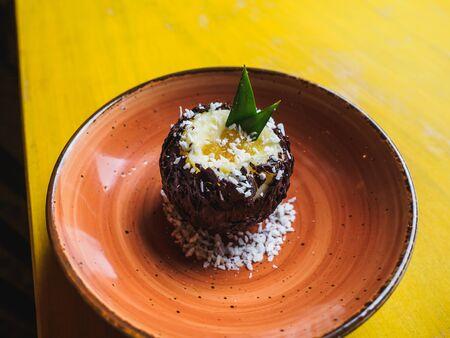 Chocolate coconut pineapple round dessert. Yellow table.