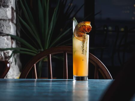 Orange tropical cocktail in hoghball glass on the blue table.