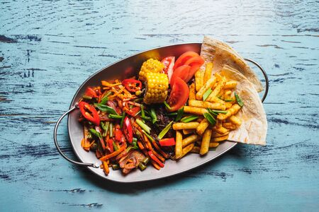 Fajitas - mexican meat with vegetables and tortilla.