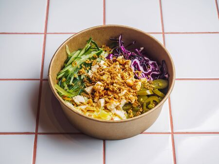 Poke bowl with chicken and vegetables on the white tile table. Stockfoto