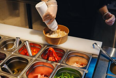 Cooking of poke bowls from ingredients in cafe. Stockfoto