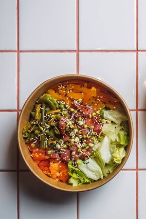 Poke bowl with tuna and vegetables on the white tile table.