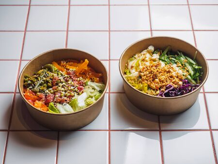 Poke bowls with meat and vegetables on the white tile table.