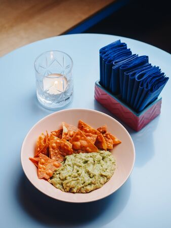 Nachos with guacamole in the plate on blue table.