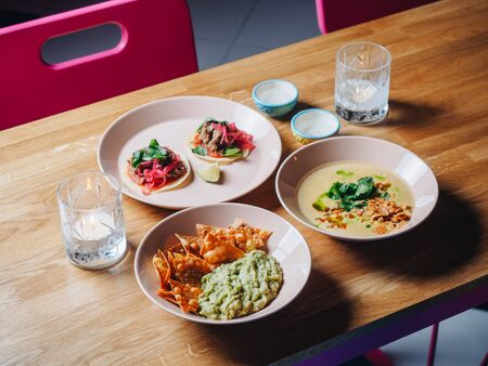 Nachos, guacamole, tacos, soup and candles on the table in cantina bar. Stockfoto