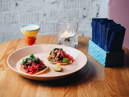 Tacos with meat, onion, greens, lime. plate on the table. Stockfoto