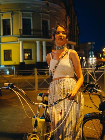 Girl with cruiser bicycle in night city street.