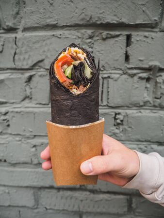 Shawarma doner roll in black pita in man hands. Stock fotó