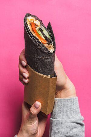 Shawarma roll with black pita on pink