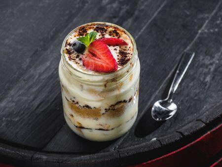 Tiramisu with berries in glass jar on the wooden barrel.