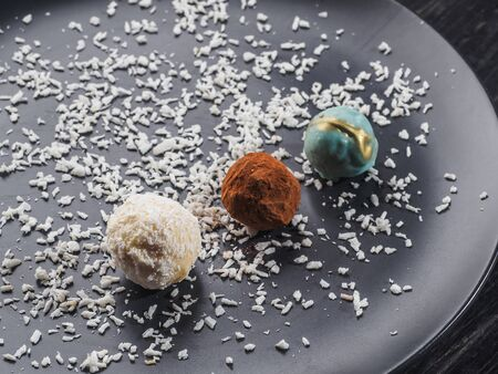 Little round coconut, truffle candys on the blue plate. Stok Fotoğraf