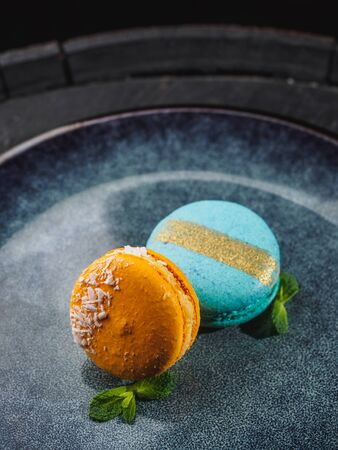 Color macaroons with mint on the blue plate.