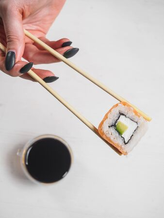 Roll with salmon, avocado and cheese in wooden chopsticks.