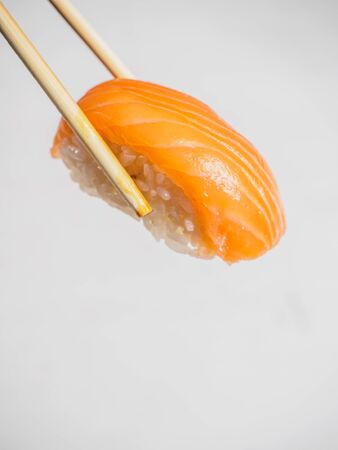 Sushi with salmon in wooden chopsticks. White background. Stock fotó