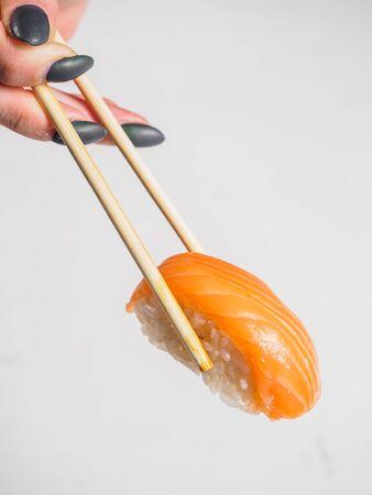 Sushi with salmon in wooden chopsticks. White background. Stok Fotoğraf