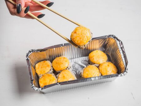 Hot cheese rolls in foil container with wooden chopsticks. Stok Fotoğraf - 148105842