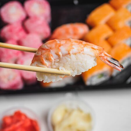 Sushi with prawn shrimp rice in wooden chopsticks.