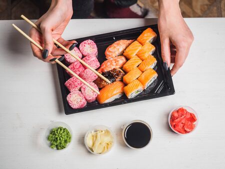 Set of sushi rolls in delivery plastic boxes on white background. Stockfoto