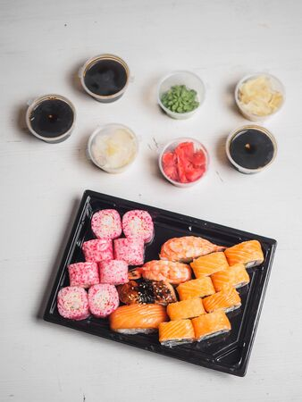 Set of sushi rolls in delivery plastic boxes on white background. Stock fotó