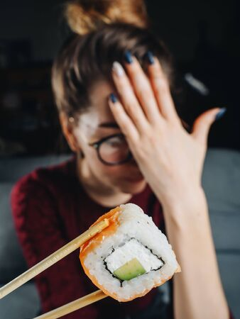 Bad negative emotions of woman with salmon roll in chopsticks.
