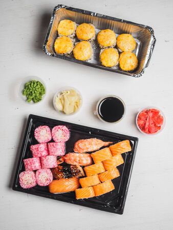 Set of sushi rolls in delivery plastic boxes on white