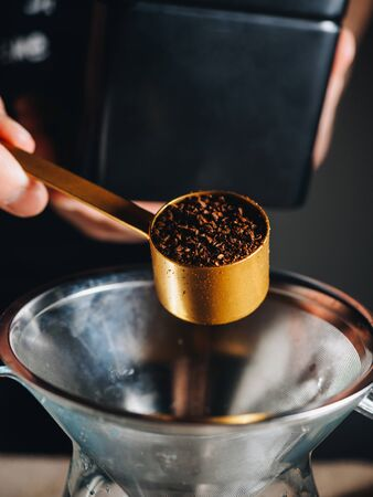 Ground coffee in measuring spoon with filter for brewing.