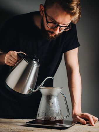Making filter coffee with kettle for brewing by man.