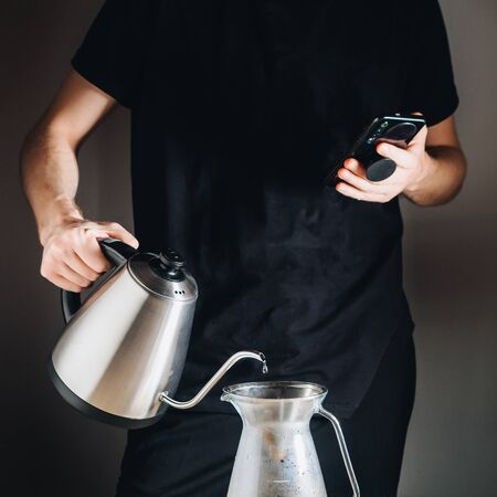 Making filter coffee with kettle for brewing by man. Stok Fotoğraf - 149175163