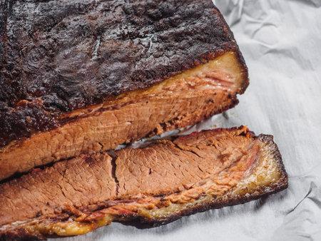 Sliced piece of beef brisket on white paper.