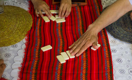 Hands of a men picking dominoes game tokens from a table Foto de archivo