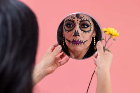 woman disguised as a catrina putting traditional Mexican food on a traditional altar of the day of the dead Standard-Bild
